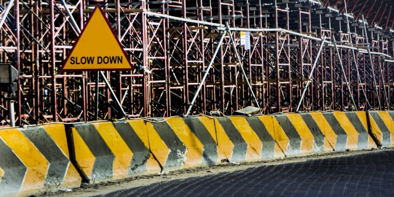 Slow Down Road Sign Yellow Black Concrete Barrier