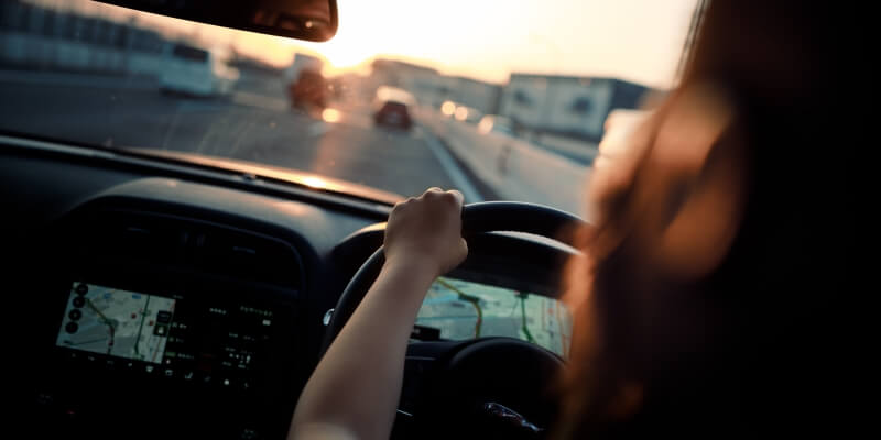 Woman Driving At Sunset